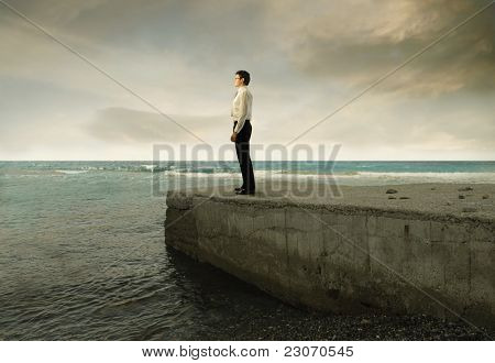 Businessman standing on a pier over the sea