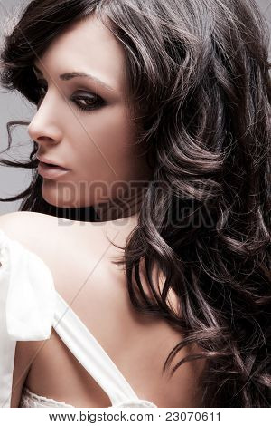 beautiful female with long wavy hair black hair, studio portrait