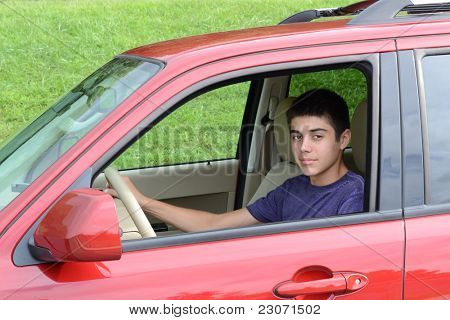 A confident newly licensed teenage male driver sits in his shiny new red car. Close up in horizontal format showing the young caucasian man as he sits behind the wheel.