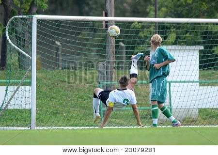 KAPOSVAR, HUNGARY - AUGUST 27: Roland Krasznai (in white) in action at the Hungarian National Championship under 18 game between Kaposvar (green) and Gyor (white) August 27, 2011 in Kaposvar, Hungary.