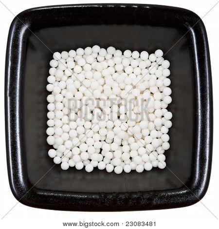 Sugar Homeopathy Balls On Black Plate Close Up