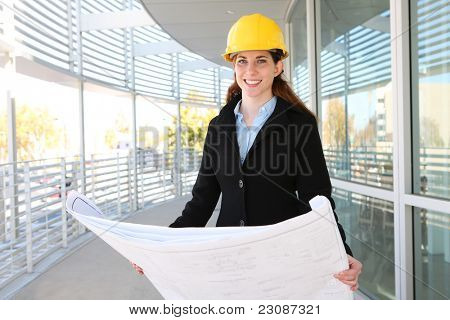 Woman Architect at work site with blueprints