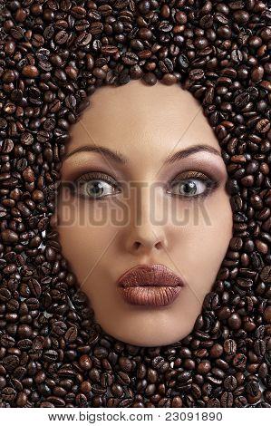 Retrato de uma menina bonita que fixa entre os grãos de café