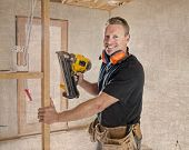 Attractive And Confident Constructor Carpenter Or Builder Man Working Wood With Electric Drill At In poster