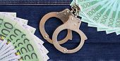 The Fan Of A Lot Of Euro Bills And Police Handcuffs Is On A Dark Denim Surface. Background Image poster