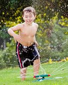 stock photo of sprinkler  - Young boy or kid cools off by playing in water sprinkler at home in his back yard on hot summer day - JPG