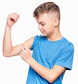 Thin Caucasian Teen Boy Wearing Blue T-shirt Showing Off His Biceps. Happy Teenager Showing His Hand poster