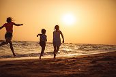 Happy Children Playing On The Beach At The Sunset Time. poster