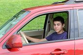 A confident newly licensed teenage male driver sits in his shiny new red car. Close up in horizontal