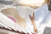 Young Lady Reading A Book In Hammock On Tropical Sandy Beach poster