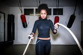 Young fit woman exercising with battle ropes during functional training indoors poster