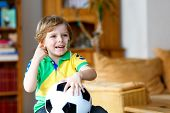 Little Blond Adorable Kid Boy With Ball Watching Soccer Football Cup Game On Tv. Funny Happy Crying  poster