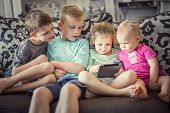 Group of kids playing with an electronic tablet devices  poster