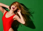 Young Happy Beautiful Sexy Woman Posing In Red Summer Fashion Body Swimsuit With Windy Hair On Green poster