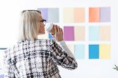 Attractive Fashion Magazine Editor Drinking Coffee And Looking At Color Palette On Wall poster