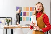 Fashion Magazine Editor With Folder In Modern Office With Colleague And Color Palette On Wall Behind poster