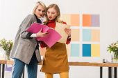 Fashionable Magazine Editors Working With Documents In Modern Office With Color Palette On Wall poster