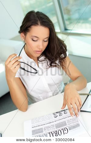 Portrait of serious business lady reading newspaper