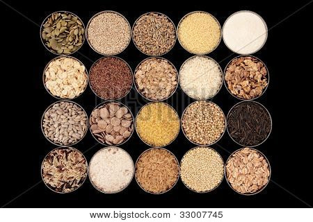 Large selection of cereal, seed and grain food in bowls over black background.