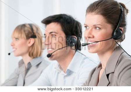 Smiling beautiful lady working at call center with colleagues in office