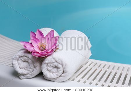 Beautiful lotus flower on towels at the edge of a pool at spa beauty club