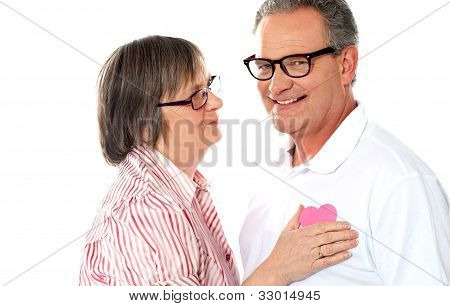 Senior Couple With Pink Heart Isolated On White