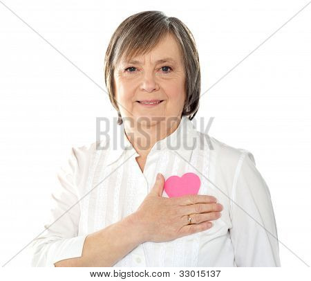 Mature Woman Holding Her Paper Heart Close To Body
