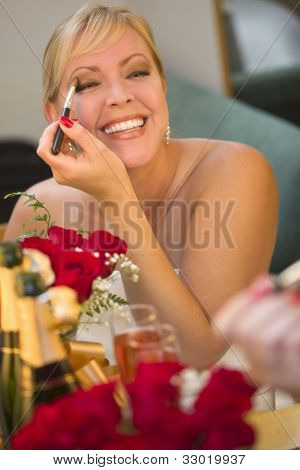 Atractiva mujer rubia aplica su maquillaje en el espejo cerca de Champagne y rosas.