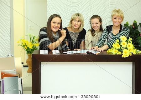 four smiling women sit in reception area with magazines and business cards and look at camera
