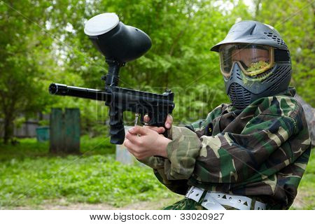 Paintball player in camouflage uniform and protective mask with traces of paintball hit sits on the ground and aims with marker into enemies.