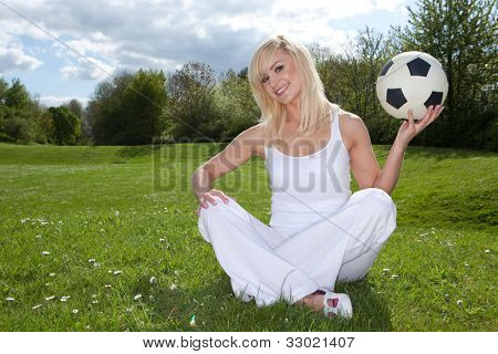 Smiling blonde woman sitting on green grass in the park about to throw a football which she is holding in her left hand