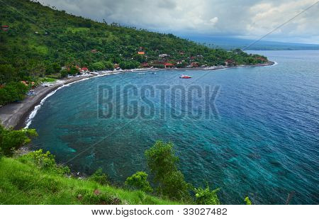 Tropical harbor with green hills around and clear blue water. Bali island (Amed)