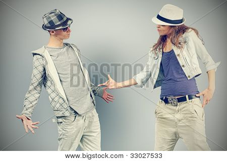 A couple of young man and woman dancing hip-hop at studio.