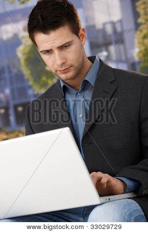 Businessman sitting outside of office, working on laptop computer, concentrating.