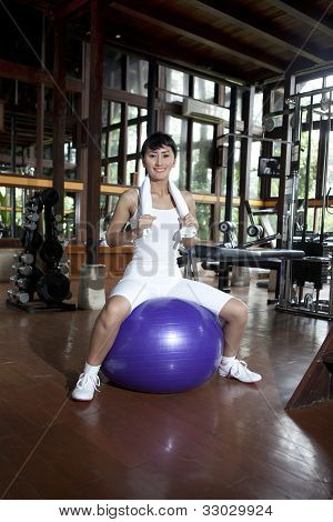 Asian Woman Posing With Swiss Ball In A Gym