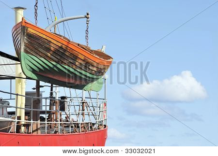 Old wooden lifeboat on side of red boat