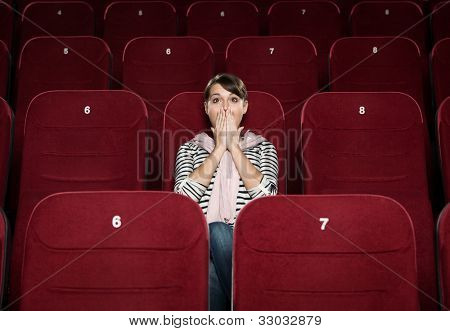 Horrified woman in the movie theater