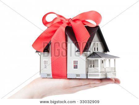 Conceito imóveis - mão segurando o modelo arquitetônico da casa com arco vermelho nele, isolado
