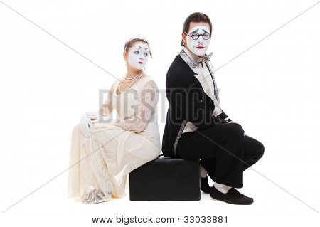 studio shot of two mimes sitting on suitcase. isolated on white