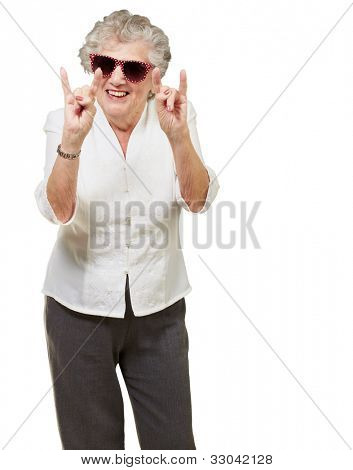 portrait of a happy senior woman doing a rock symbol over a white background