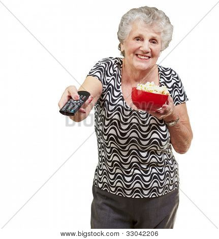 portrait of a happy senior woman looking at the tv over a white background