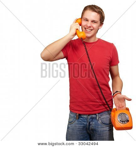 portrait of a young man talking with a vintage telephone over a white background
