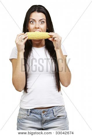 woman tasting a delicious corncob against a white background