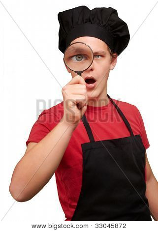 portrait of a young cook man looking through a magnifying glass over a white background