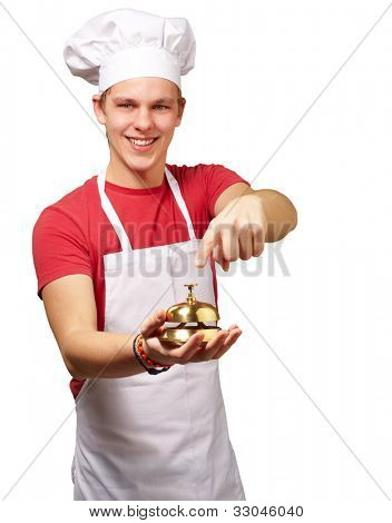 portrait of a young cook man pressing a golden bell over a white background