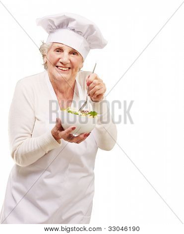portrait of an adorable senior cook woman eating a salad against a white background