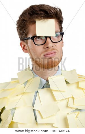 Unhappy young man with a sticky note on his face, covered with yellow stickers, isolated on white