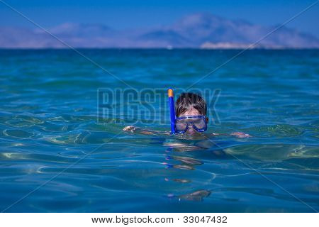 Little boy in a sea with mask and snorkel