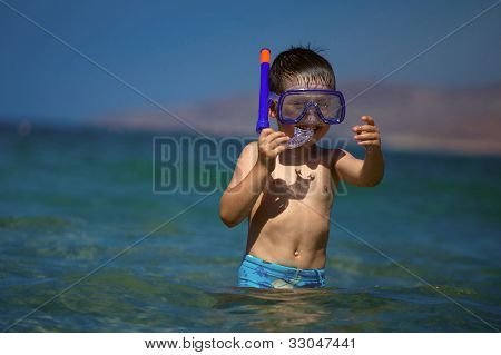 Boy in sea with a swimming mask and snorkel