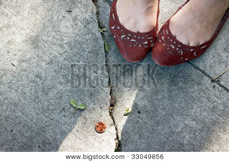 Girl finds a penny on the sidewalk.